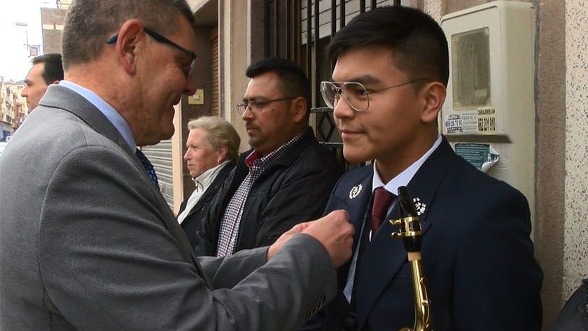 Juan José Mira coloca el pin a uno de los nuevos músicos